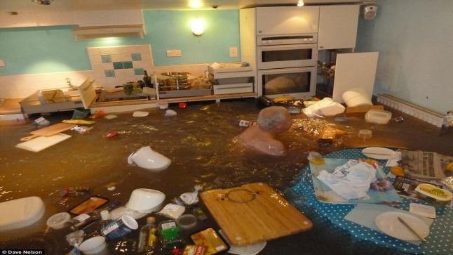 متقاعد يقدم على السباحة في مطبخه بعد أن غمرت مياه الفيضانات منزله